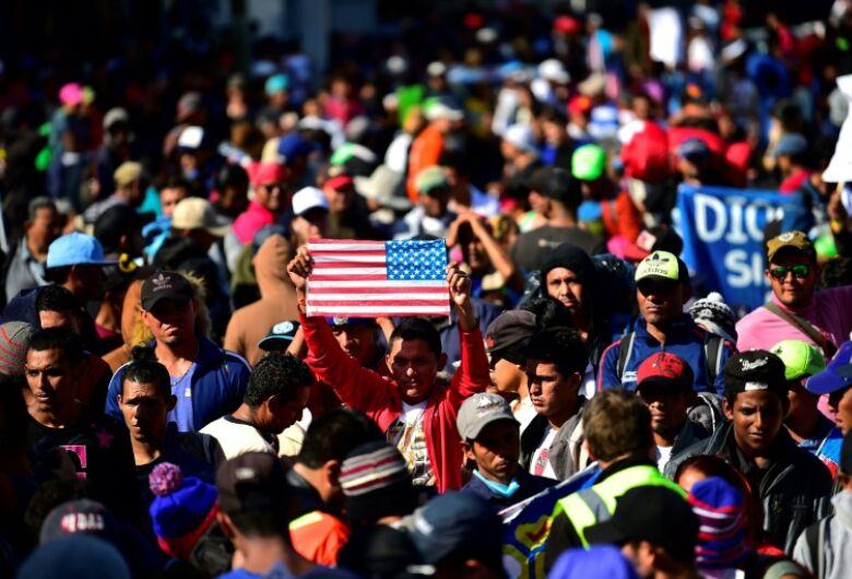 Centenas de migrantes tentam pular cerca fronteiriça entre México e EUA