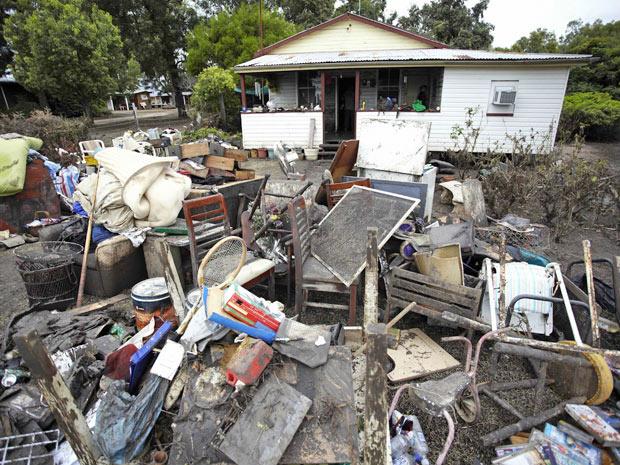 Objetos são empilhados em frente de casa em Condamine após enchente - Crédito: Foto: Dean Saffron/AP