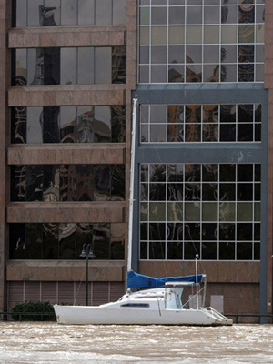 Barco passa por rua alagada nesta quarta-feira  - Crédito: Foto: AFP