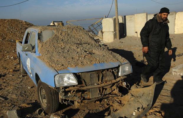 Militante do Hamas ao lado de carro coberto por terra após bombardeio israelense nesta quarta-feira - Crédito: Foto: Reuters