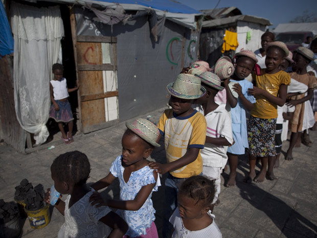 Crianças haitianas formam fila em campo de refugiados na capital Porto Príncipe. - Crédito: Foto: Associated Press