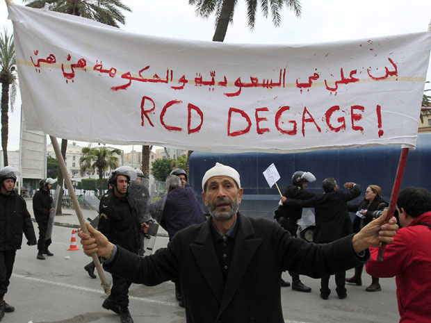 Manifestante segura faixa que pede a saída do RCD, partido do presidente deposto Zine al-Abidine Ben Ali, do novo governo interino, durante protestos nesta terça - Crédito: Foto: Zohra Bensemra / Reuters