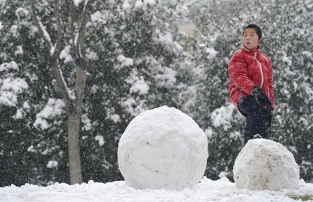 Menino brinca durante nevasca em parque de Xangai nesta quinta-feira - Crédito: Foto: AFP