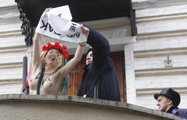 Policial impede protesto solitário de ativista seminua em frente à Embaixada do Egito na Ucrânia, em Kiev, nesta quarta-feira - Crédito: Foto: Reuters