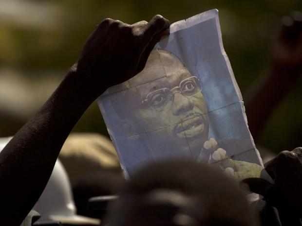 Manifestante favorável a Aristide acena foto do ex-presidente durante protesto nesta segunda-feira - Crédito: Foto: AP