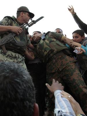 Militar é beijado por manifestantes antigoverno nesta quinta-feira - Crédito: Foto: AP