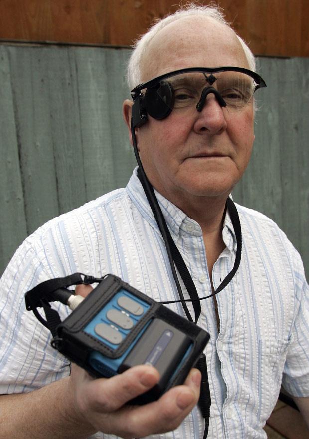 O britânico Eric Selby, de 68 anos, utiliza uma câmera acoplada aos óculos para poder enxergar. O aparelho está ligado a um implante de retina artificial. O kit também com um computador e um transmissor, que trabalham em conjunto com a retina, conhecida c - Crédito: Foto: Martin Cleaver / AP Photo