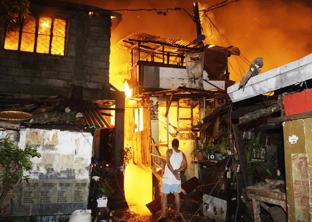 Homem observa fogo consumir sua casa durante incêndio em favela em Quezon, subúrbio de Manila, capital das Filipinas, nesta terça-feira - Crédito: Foto: AP