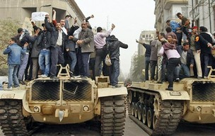 Manifestantes egípcios exigindo a derrubada do presidente Hosni Mubarak em cima de tanques do exército egípcio no Cairo - Crédito: Foto: M. Abed/AFP