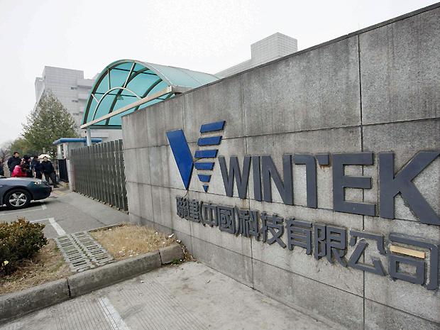 Pessoas em frete a uma fábrica de propriedade da Wintek, empresa taiuanesa que produz telas sensíveis ao toque para a Apple, em Suzhou, na província de Jiangsu, na sexta-feira - Crédito: Foto: Reuters
