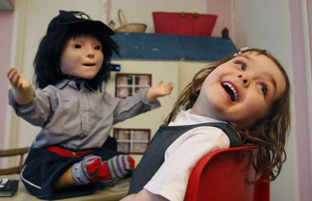 A garota Eden Sawczenko brinca com o robô Kasper, durante pesquisa em Hatfield, na Inglaterra. O robô está sendo usado para ajudar crianças autistas em uma creche em Stevenage, em sessões semanais de terapia. As crianças brincam com o robô, controlado rem - Crédito: Foto: AP