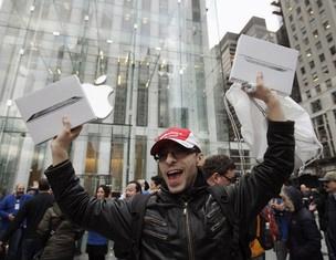 Consumidor mostra duas caixas do iPad 2 após sair da loja da Apple na 5ª Avenida, em Nova York  - Crédito: Foto: Reuters