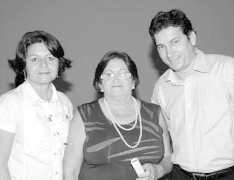 Recebendo das mãos de Ivonete e do vereador Dalgomir Buraqui a homenagem pelo Dia da Mulher, a senhora Araci, telefonista da Prefeitura de Ivinhema. -