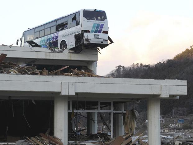 Um ônibus foi parar em cima de um prédio em Ishinomaki, na província de Miyagi, no Japão, após o terremoto e o tsunami que atingiram o país no último dia 11; o governo japonês estima que os danos sejam de cerca de US$ 310 bilhões - Crédito: Foto: AP