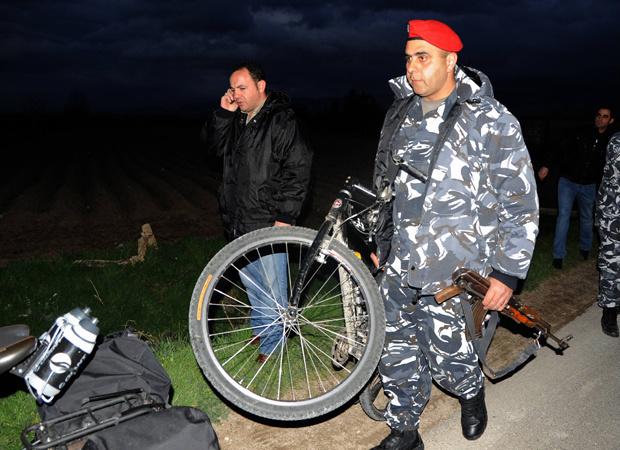 Policial carrega bicicleta de um dos sequestrados nesta quarta-feira - Crédito: Foto: Reuters