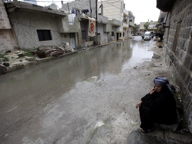 Mulher observa rua vazia na cidade de Deraa, na Síria, perto da mesquita Al Omari - Crédito: Foto: Hussein Malla/AP