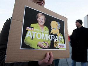 Manifestante segura cartaz com a chanceler alemã Angela Merkel e o personagem dos \'Simpsons\' Sr. Burns, dono de uma usina de energia nuclear  - Crédito: Foto: John Macdougall/AFP
