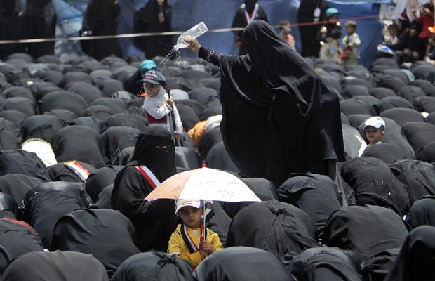 Mulher refresca manifestantes durante oração nesta quinta-feira - Crédito: Foto: AP