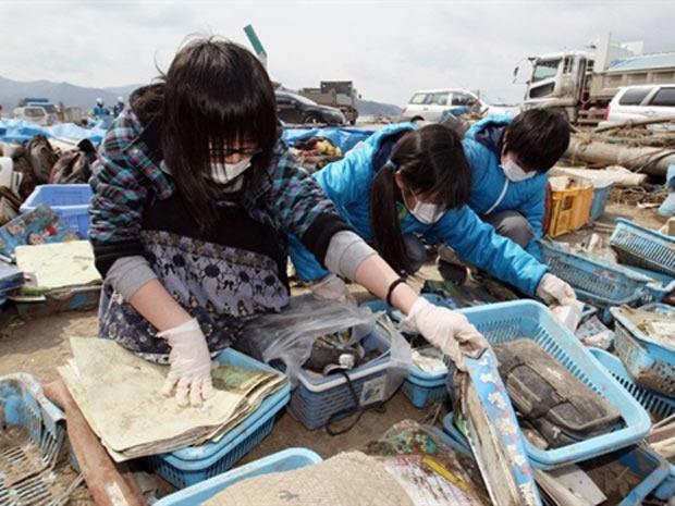 Crianças procuram por seus pertences em escombros de escola em região devastada de Ishinomaki, cidade da província de Miyagi - Crédito: Foto: AFP