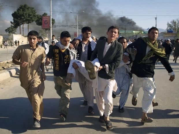 Grupo carrega ferido em ataque a sede da ONU em Mazar-i-Sharif, no Afeganistão - Crédito: Foto: Mustafa Najafizada / AP