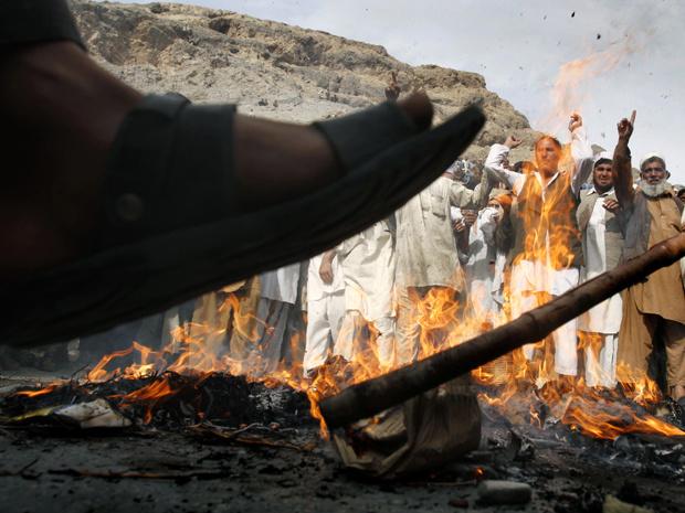 Manifestante pisa sobre o que sobrou de boneco representando o pastor Terry Jones, queimado nesta segunda-feira - Crédito: Foto: AP