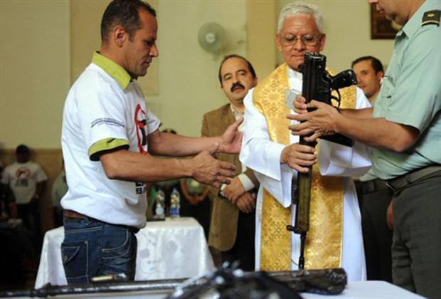Membro de quadrilha de favela da cidade de Medellín, na Colômbia, entrega armas para padre durante cerimônia em igreja nesta segunda-feira - Crédito: Foto: AFP