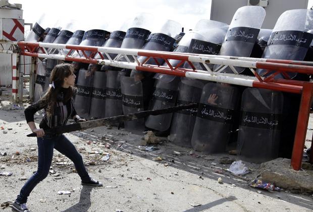 Parente de preso na cadeia da cidade libanesa de Roumieh encara policiais de choque na frente do complexo prisional durante protesto nesta quarta-feira - Crédito: Foto: AP