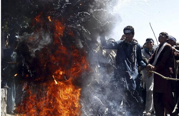 Afegãos queimam bandeiras dos EUA na estrada entre Cabul e Jalalabad, nesta terça-feira - Crédito: Foto: Reuters