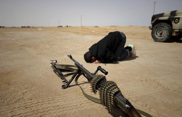 Rebelde ora no front de batalha próximo à cidade líbia de Brega nesta quarta-feira - Crédito: Foto: AP