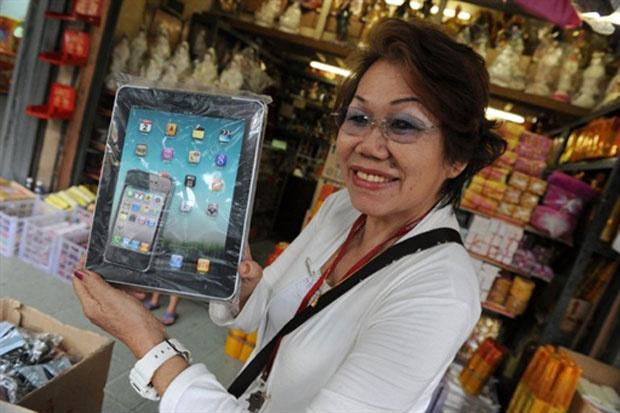 Réplicas do tablet IPad e do celuar iPhone viraram oferendas entregue aos mortos da Malásia. As peças, que custam cerca de US$ 1 são queimadas em homenagem aos parentes falecidos. Além dos gadgets da Apple, são oferecidas réplicas de TVs de LCD, computado - Crédito: Foto: Roslan Rahman/AFP