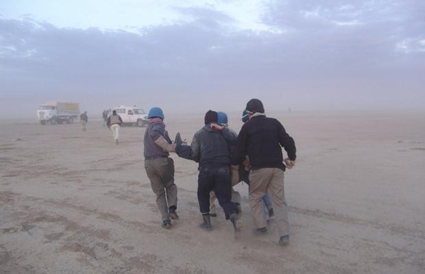 Militantes levam companheiro ferido nesta sexta-feira - Crédito: Foto: Reuters