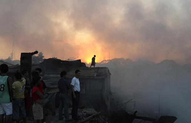 Moradores observam chamas que destruíram favela no subúrbio de Quezon, nordeste de Manila, capital das Filipinas, nesta segunda-feira - Crédito: Foto: AP