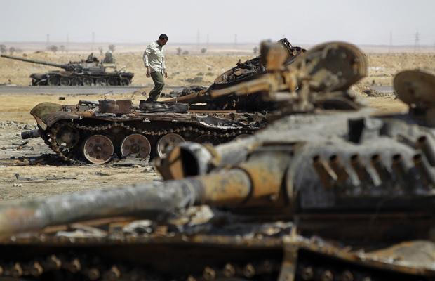 Rebelde caminha entre tanques destruídos das tropas de Kadhafi nesta terça-feira - Crédito: Foto: AP