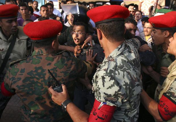 Soldados retiram manifestantes que bloqueavam rua na região da Praça Tahrir, no Cairo, nesta terça-feira - Crédito: Foto: AP