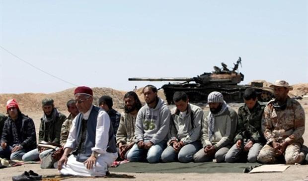 Rebeldes líbios fazem juntos as orações de meio-dia próximo ao portão de entrada da cidade de Ajdabiya - Crédito: Foto: Marwan Naamani / AFP