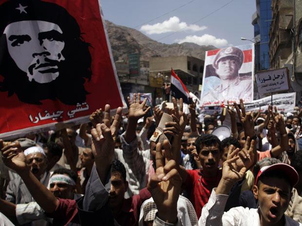 Manifestantes carregam posteres do líder revolucionário Che Guevara e do ex-presidente do Iêmen do Norte, Ibrahim al-Hamdi, durante protesto em Taiz, no sul do país - Crédito: Foto: Khaled Abdullah / Reuters