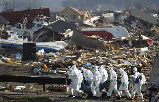 Policiais japoneses em roupas especiais fazem buscas por corpos na região de Fukushima - Crédito: Foto: AP