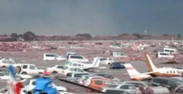 Imagem divulgada pela Guarda Costeira mostra o tsunami varrendo carros e aeronaves - Crédito: Foto: BBC