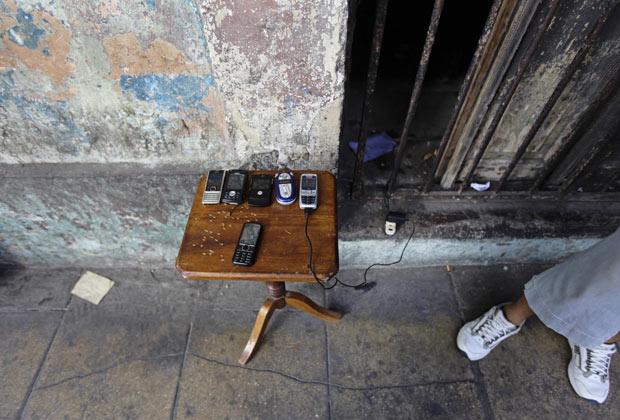 Ambulante vende telefones celulares usados em rua de Havana nesta segunda-feira - Crédito: Foto: AP