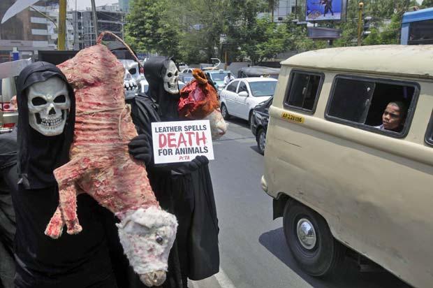 Criança indiana observa ativistas com carcaça falsa de animal e placa com dizeres \'couro significa morte para os animais\' - Crédito: Foto: Mahesh Kumar A./AP