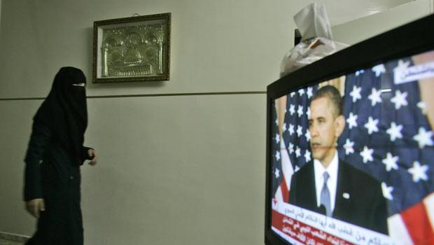 Palestina passa em frente a TV que passa discurso de Obama nesta quinta-feira - Crédito: Foto: AP
