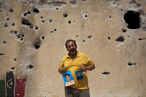 Em frente a parede com buracos de tiros em Misrata, homem mostra fotos de dois filhos desaparecidos há dois meses, segundo ele levados por forças ligadas a Muammar Kadhafi. - Crédito: Foto: AP