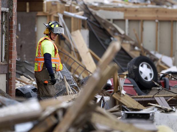 Bombeiro observa carro virado entre escombros nesta quinta-feira - Crédito: Foto: AP