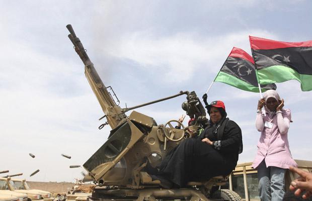 Mulher observa rebelde ensinando uso de arma em Benghazi nesta quarta-feira - Crédito: Foto: AP