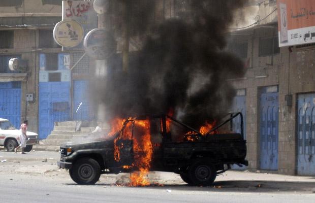 Carro da polícia é queimado durante confrontos nesta sexta-feira - Crédito: Foto: AP