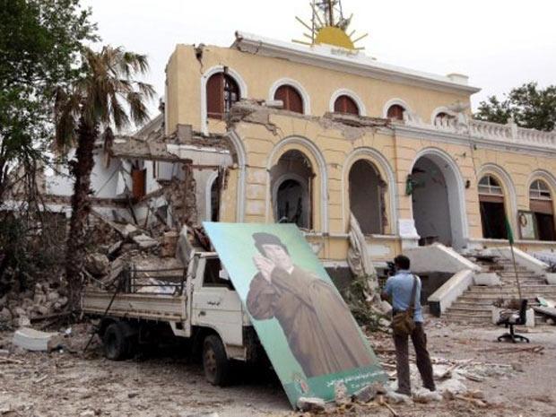 Foto de Muammar Kadhafi é vista do lado de fora do Parlamamento líbio parcialmente destruído, nesta segunda - Crédito: Foto: Mahmud Turkia / AFP