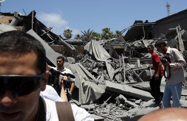 Jornalistas visitam o que seriam as ruínas de um hotel destruído por ataque da Otan a Trípoli, capital da Líbia, nesta quinta-feira - Crédito: Foto: AP