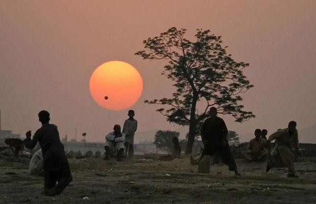 Refugiados afegãos jogam cricket em favela de Islamabad, no Paquistão - Crédito: Foto: Anjum Naveed/AP