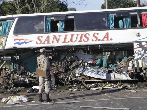 Policial observa destroços de ônibus envolvido em acidente com caminhão próximo a Ypacaraí, no Paraguai - Crédito: Foto: Jorge Saenz / AP