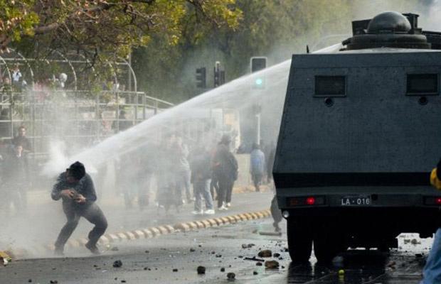 Polícia lança jato d'água contra manifestante em Santiago do Chile nesta quinta-feira - Crédito: Foto: AFP